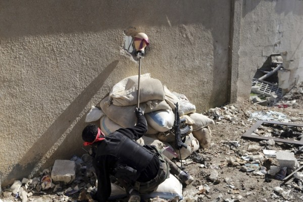 Боец Свободной сирийской армии пытается выманить снайпера во время столкновения с регулярными войсками в пригороде Дамаска.