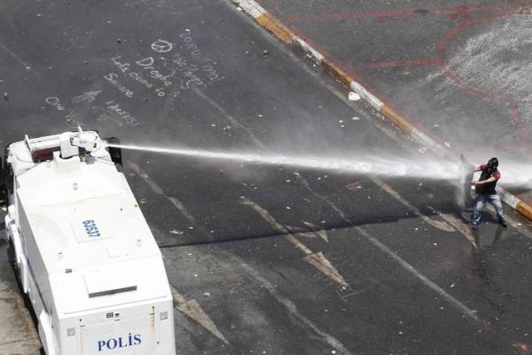 Полиция применяет водометы и слезоточивый газ, разгоняя протестующих на площади Таксим, Стамбул, Турция.