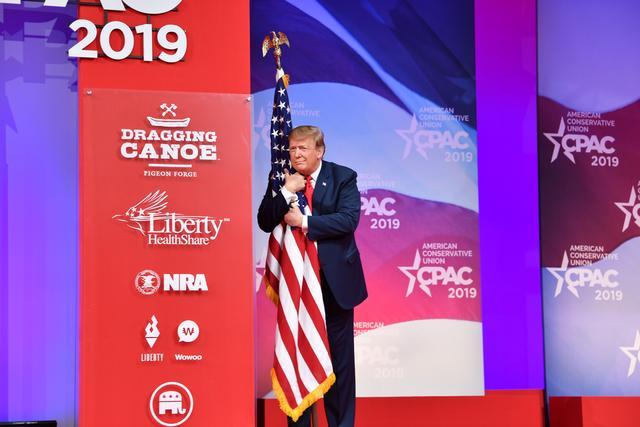 Трамп обнимает флаг.