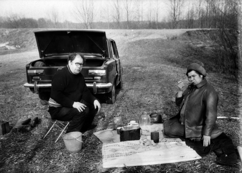Мои родители на пикнике. Еще невесь снег расстаял. Какая-то каша или картошка, наверное с тушонкой, хлеб, лук, солености в банке.