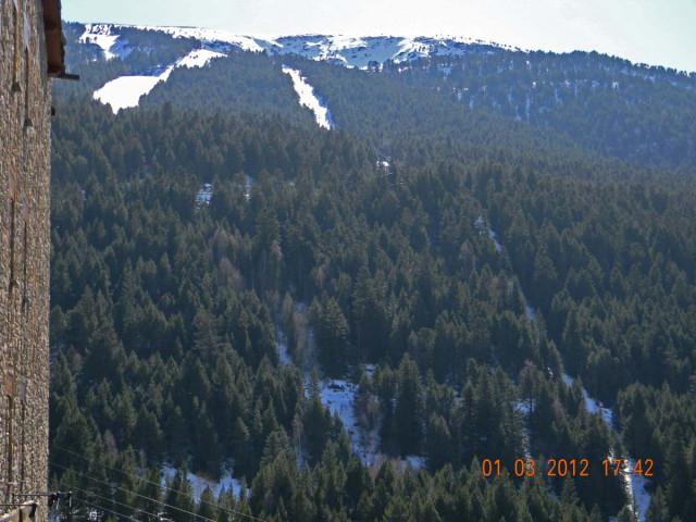 Из окна гостиницы видны горнолыжники. Но основная зона катания - за этой горой.