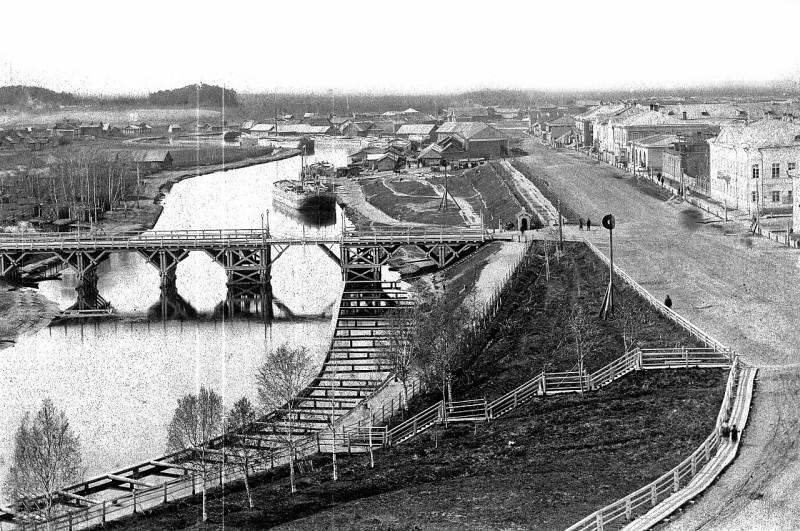 Конец 1880-х годов. Деревца еще небольшие. На берегу установлена мачта со знаком для судов. У моста — караульная будка. Хорошо виден бечёвник