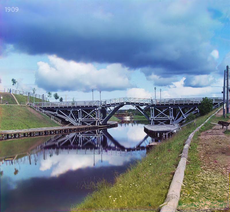 Реставрация: В. Ратников. Справа — бечевник, слева возвышенность — так называемая Красная горка, вдалеке за мостом видна баржа