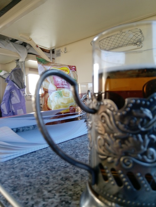 Пюре, пиво в припаянном стакане, походная тетрадь и бордюр на столе
