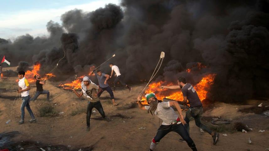 Палестинцы бросают камни во время акции протеста на границе сектора Газа с Израилем 5 октября 2018 года. Халил Хамра / AP