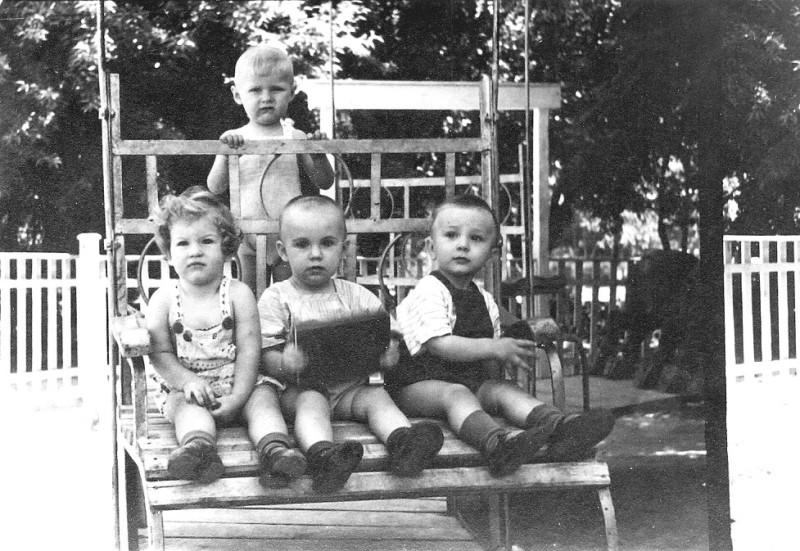 Вот, кто не верит, документальное подтверждение: июль 1954 года, мне без месяца 2 года. И мы с друзьями, которые сидят передо мной рядком, мчимся на карусели, которую во всю силу крутит мой папа, в нашем любимом парке Тельмана!