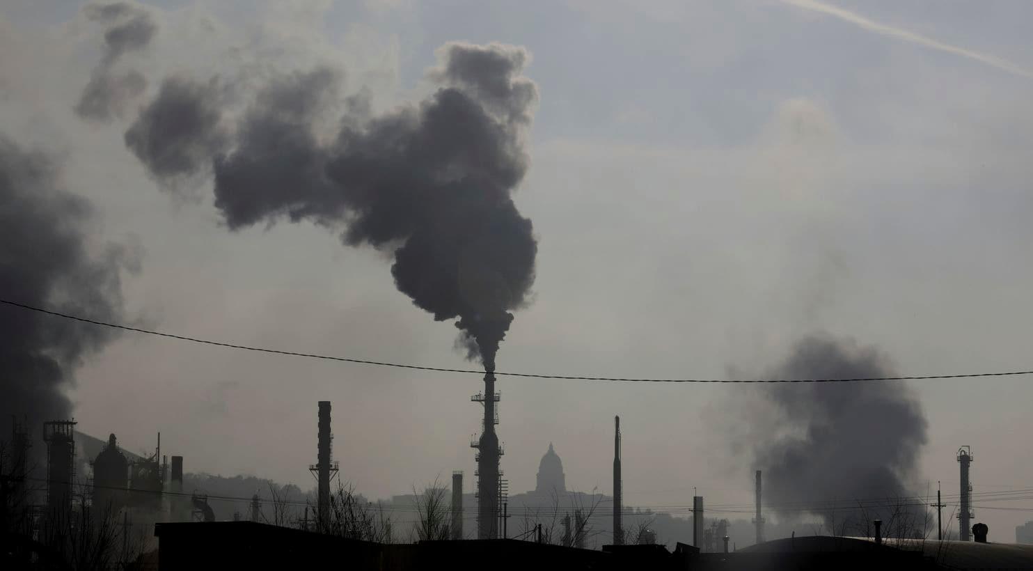 Дымовые трубы возле нефтеперерабатывающего завода видны перед Капитолием штата Юта 10 декабря 2018 года. Новое исследование, опубликованное 11 марта, говорит, что афроамериканцы и латиноамериканцы вдыхают гораздо больше смертельно загрязненного воздуха, чем они несут за это ответственность. (Рик Баумер / AP)