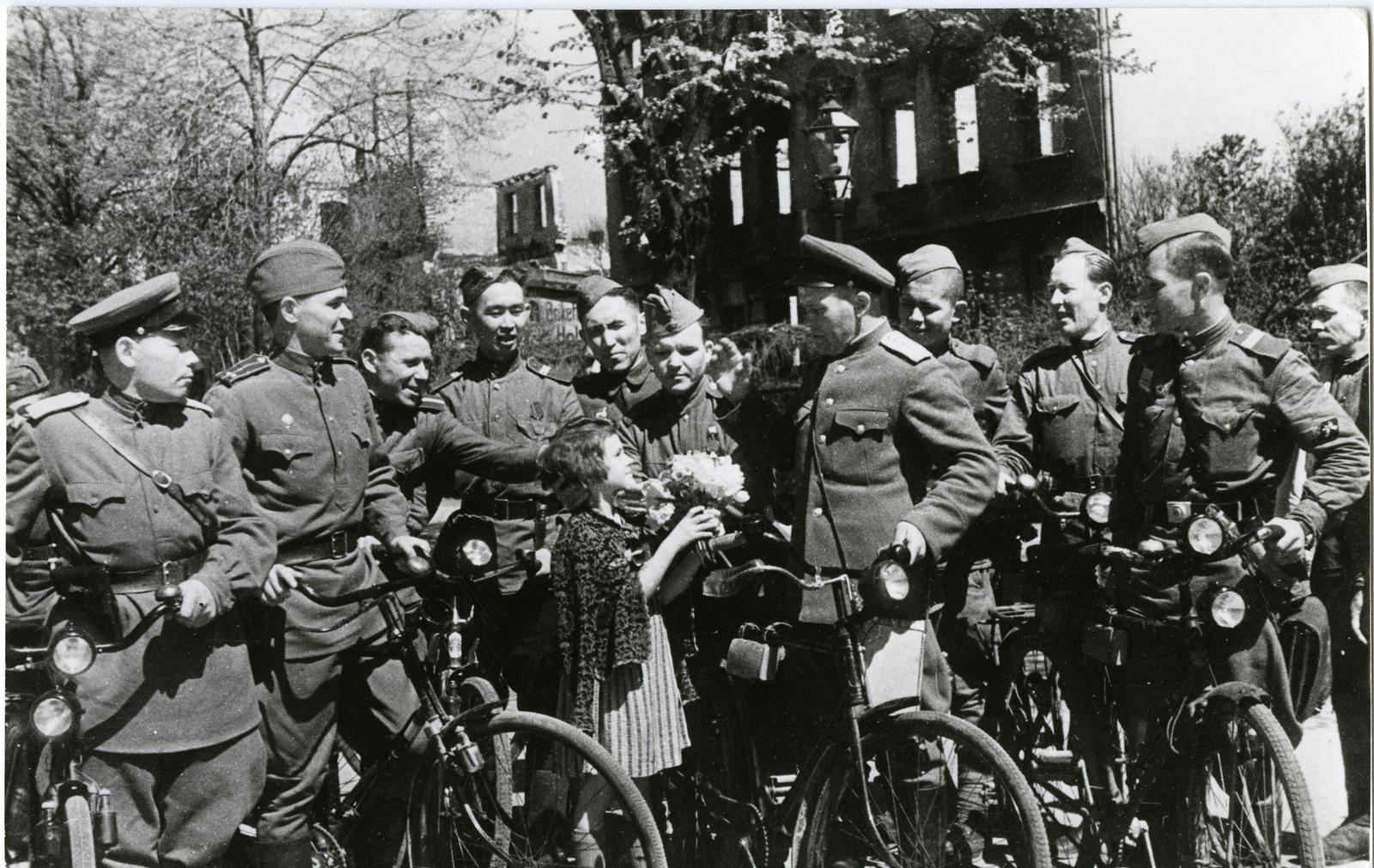 Немецкая девочка дарит цветы советским солдатам. Кёнигсберг. Июнь 1945 года. Автор Савин М. И. КОИХМ