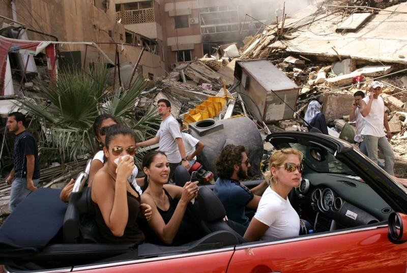 Young Lebanese drive through devastated neighborhood of South Beirut, 15 August