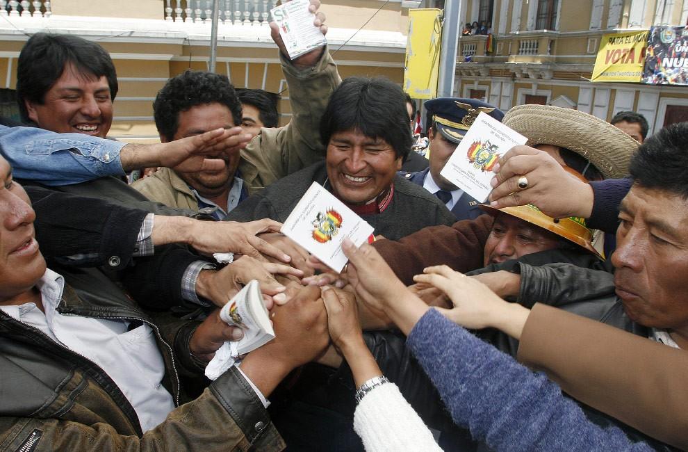 Президент Эво Моралес раздает копии новой Конституции во время демонстрации вне правительственного дворца