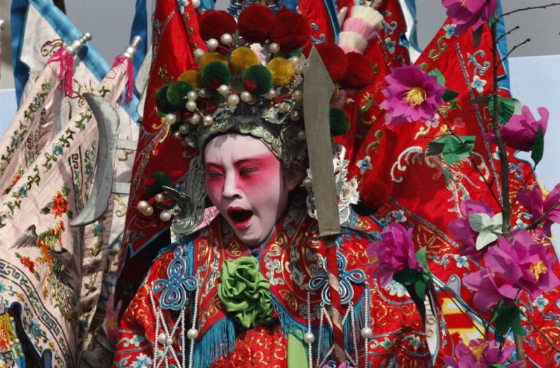 Местный актер, наряженный в стиле китайской мифологии, зевает