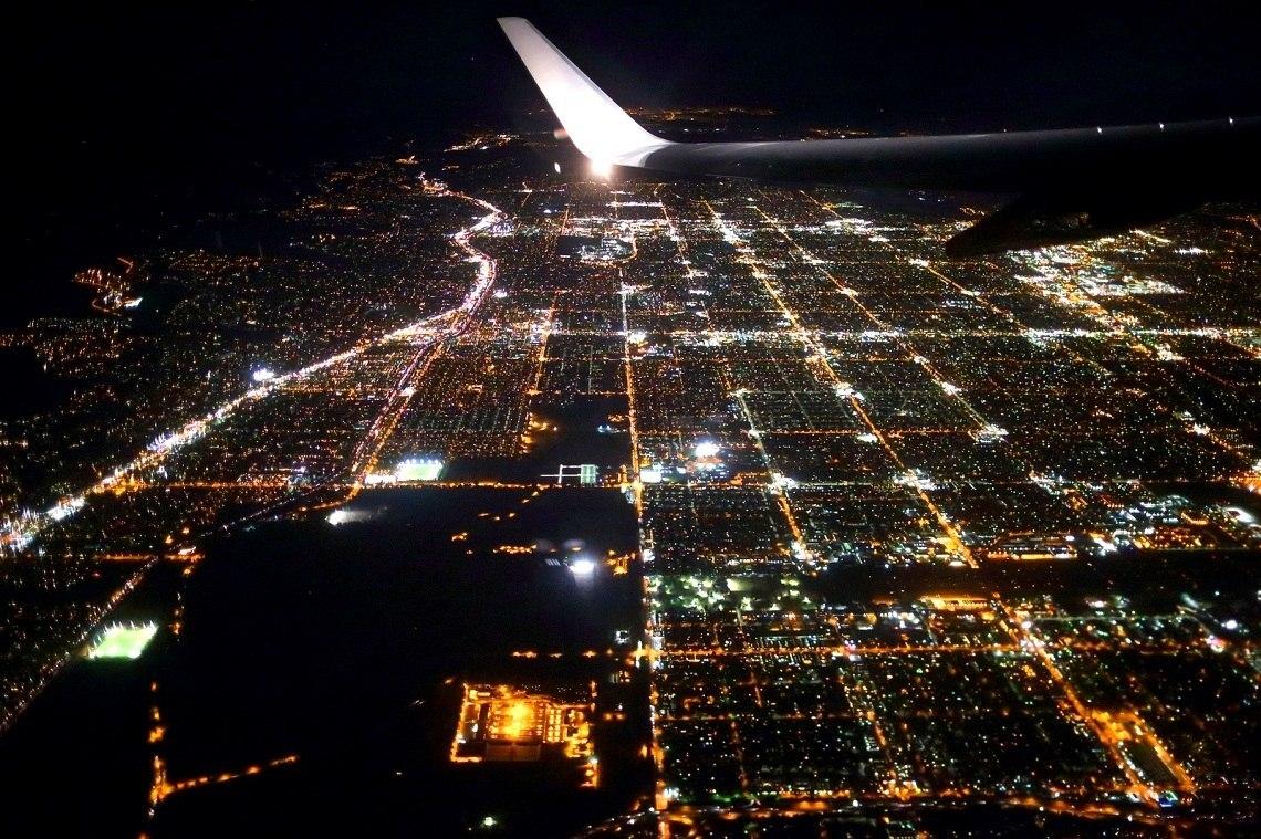 Вид из иллюминатора авиалайнера на город