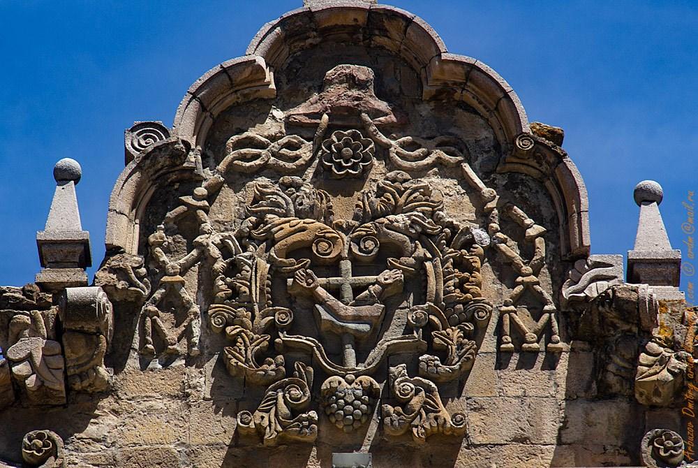 Сркещенные руки на фасаде - символ францисканцев