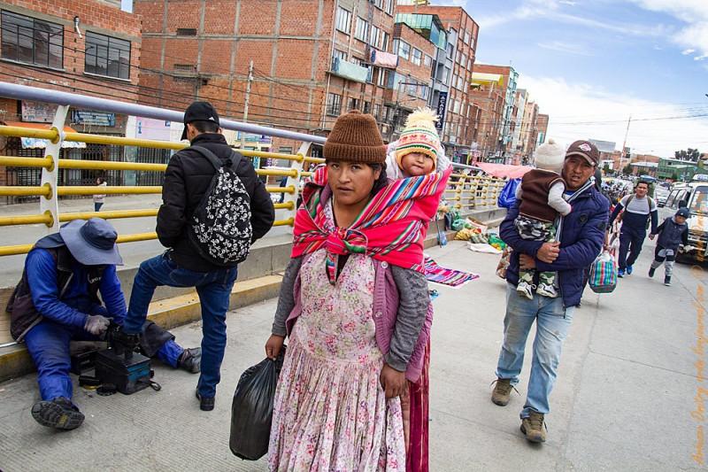 Боливийка несет ребенка в традиционном тканном одеяле - агуайо.