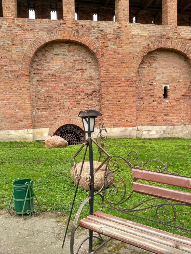 Лавочка для отдыха на фоне уцелевшего участка крепостной стены. Таких украшений в саду много и они все разные!