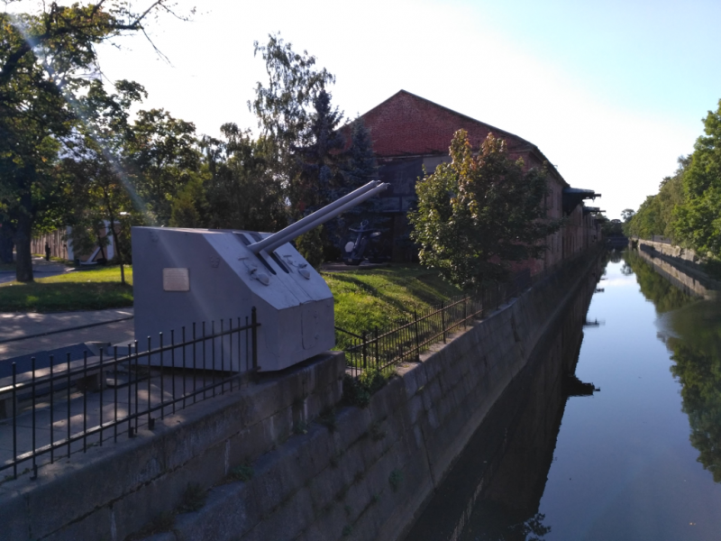 На заднем плане, у стены одного из корпусов кронштадтского Адмиралтейства, установлены два якоря и кусок брони с того же линкора