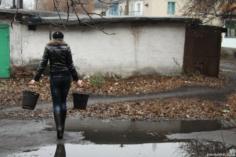 Запас угля хранится в угольных сараях. Девушка с вёдрами идет в свой сарай за углем.