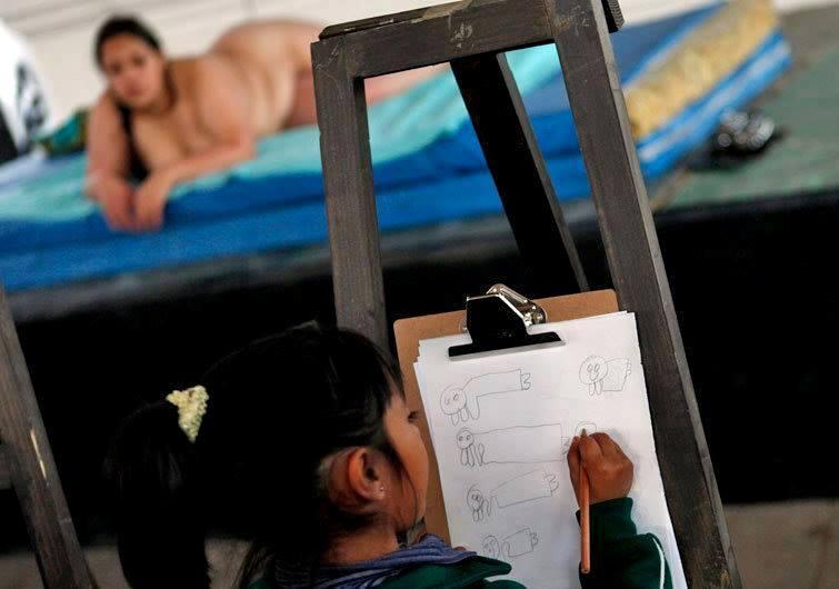 Ученица художественной школы в Мексике рисует с натуры женщину.