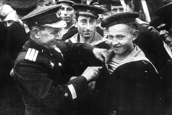 Командир бригады торпедных катеров Северного флота А.В. Кузьмин вручает юнге Саше Ковалеву (04.01.1927 — 09.05.1944) орден Красной Звезды. 01.05.1944