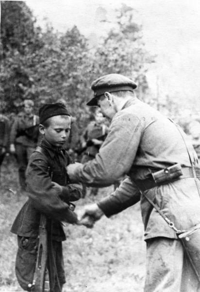 Командир партизанского отряда вручает медаль «За отвагу» юному партизану-разведчику. 1942 г.