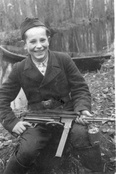 Портрет 15-летнего партизана-разведчика Миши Петрова из отряда имени Сталина с трофеями. Белоруссия, 1943 г.