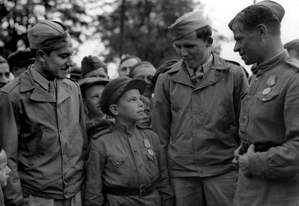 Сержант С. Вайншенкер и техник-сержант Вильям Топпс с сыном полка-10-ти лет, 169 авиабазы особ.назначения.Служил пом.техника по вооружению. Аэродром Полтава.1944 г.