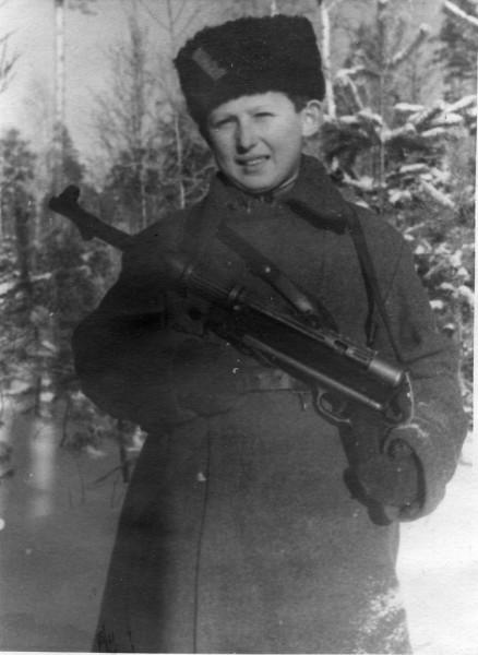 Советский партизан-подросток Коля Любичев из партизанского соединения А.Ф. Федорова с трофейным немецким 9-мм пистолетом-пулеметом МР-38 в зимнем лесу. 1943 г.
