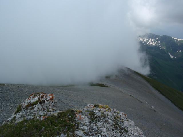 Из-за Загеданского хребта наползает туман. Низом осыпи есть натоптанная тропа, но только заканчивается она там, где на фото визуально заканчивается осыпь...