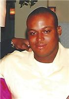 Photo of a man with dark skin and a buzz cut, smiling slightly.