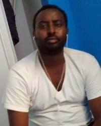 Photo of Abdirahman Abdi, a man with very dark skin and short curly black hair. He is wearing a white T-shirt and has earbuds in his ears.