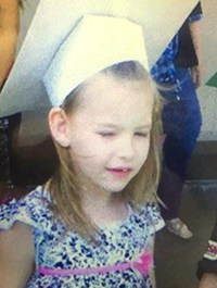 Photo of Alexis Wartena. She is a small girl with fair skin and light blonde hair. She is wearing a white graduation cap and black-and-white polka-dotted dress.