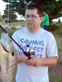 Photo of Joey Weber. He is standing outdoors near a pond, holding a fishing rod with a fish hanging from it. Joey is a young man with short brown hair and fair skin, wearing a T-shirt and jeans.
