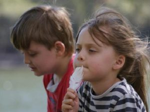 Photo of Martin and Elisa. They are children with brown hair, photographed outdoors. Martin is wearing a red sweater and looking away to the left. Elisa has long, tangled hair; she is holding a feather up to her lips.