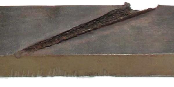 Отверстие, пробиваемое в броне кумулятивной струёй. Разрез брони вдоль отверстия.