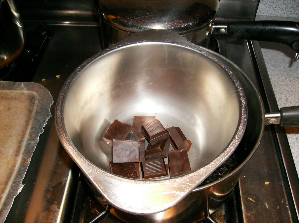 Squares of dark chocolate begin to melt in the stainless-steel bowl.