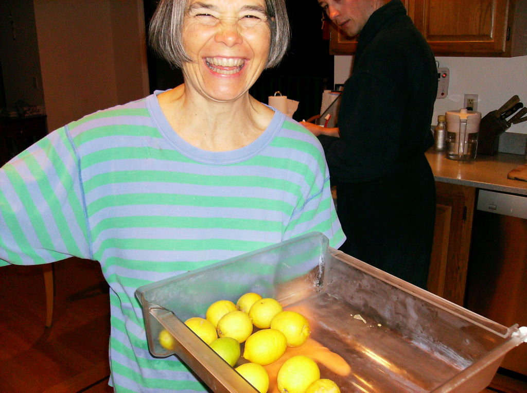 My aunt is a tiny woman in her mid-50s with salt and pepper hair in a tapered pageboy bob. She is laughing so hard her eyes are half-shut. She is wearing a knit blue and green striped pajama top and holds a crisper drawer full of lemons.