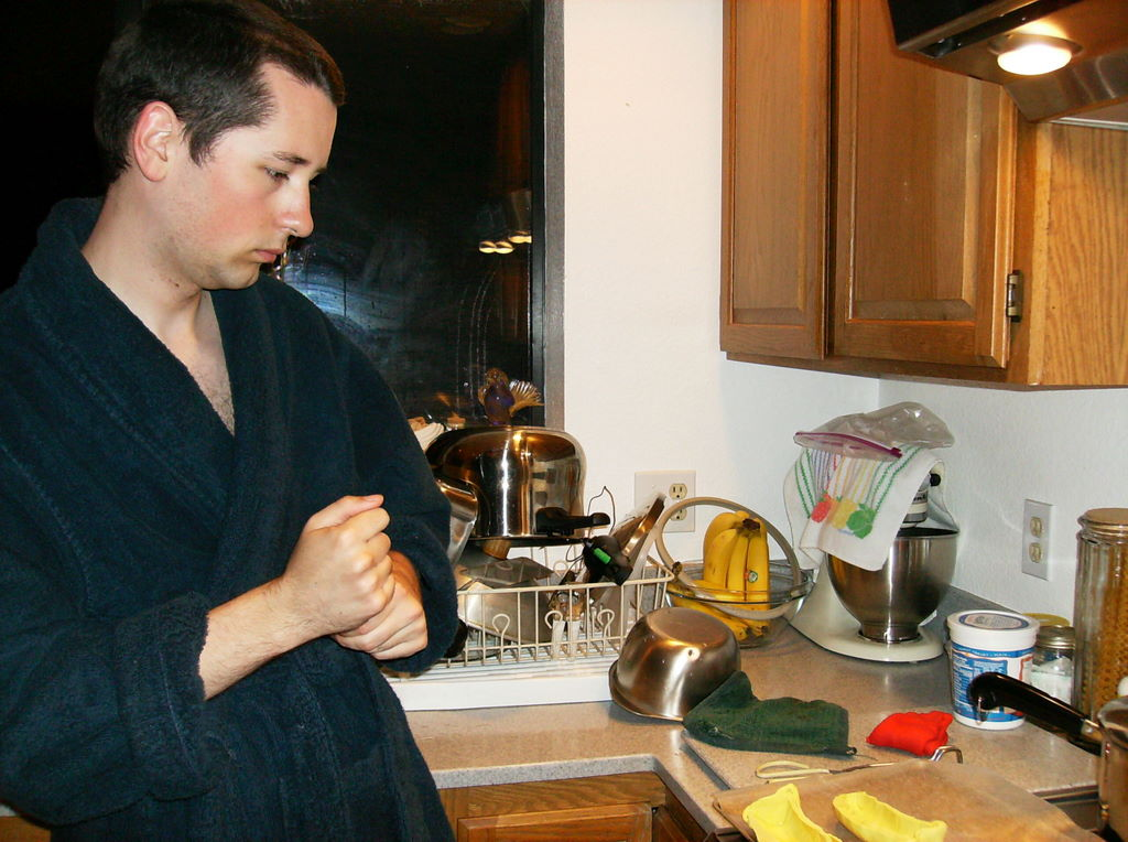 My cousin squeezes modeling clay unseen in his clenched fists; a larger hunk of red modeling clay sits on the counter.
