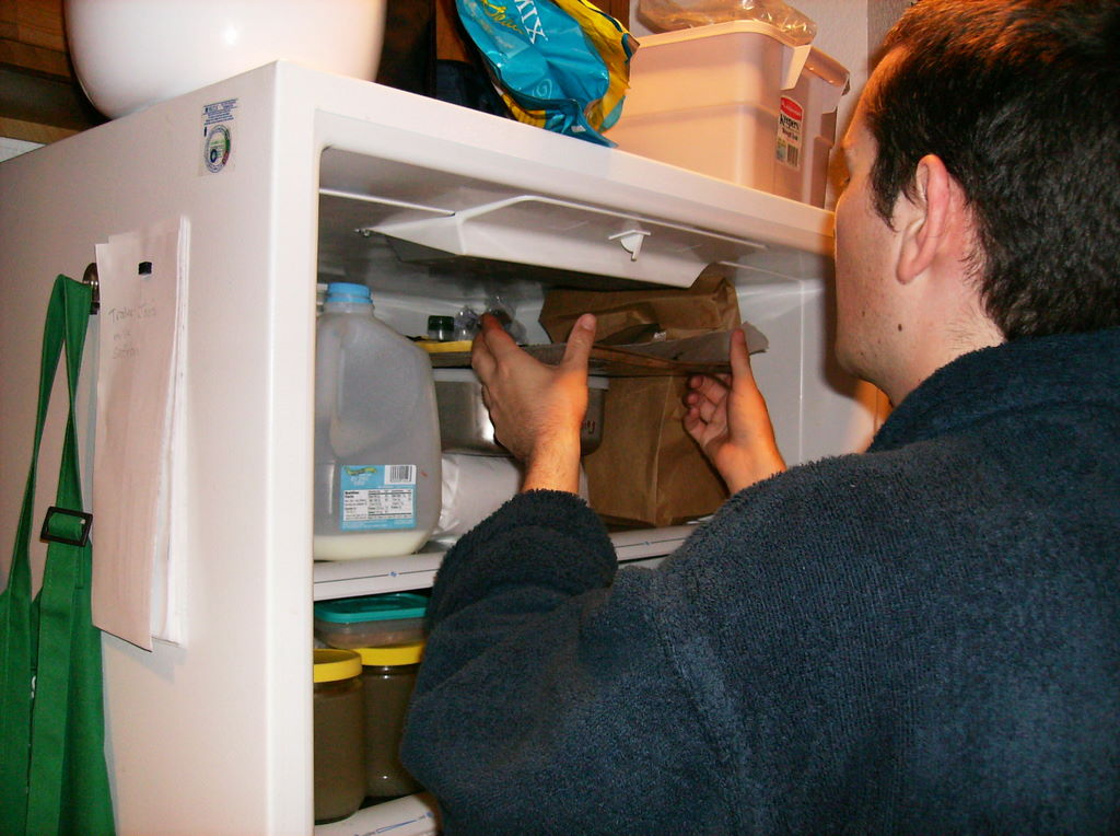 My cousin slides the tray into the refrigerator, balancing it on top of a metal food storage box in there.