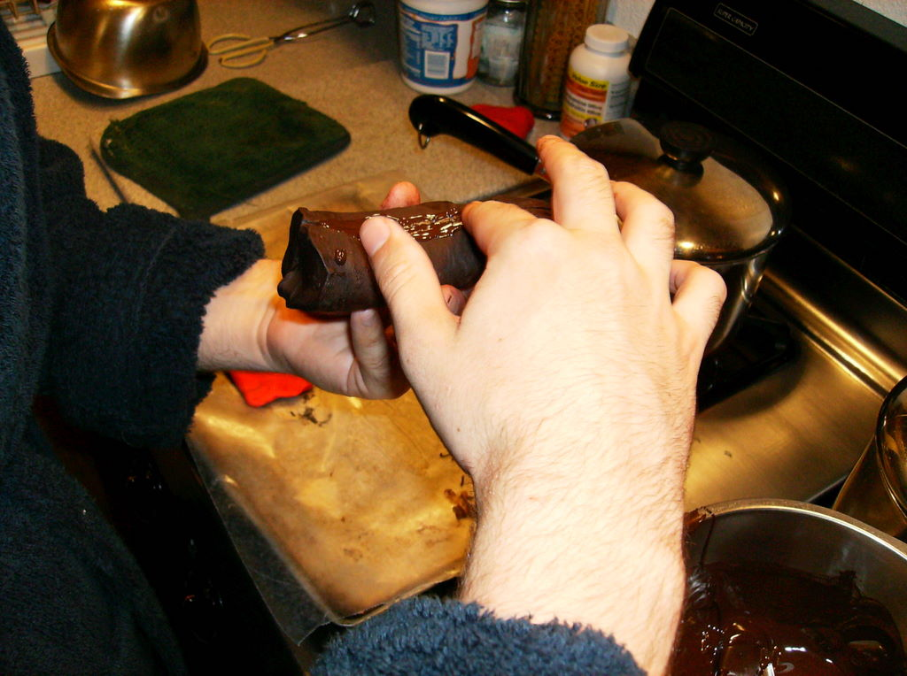 My cousin smooths molten chocolate into the crack.
