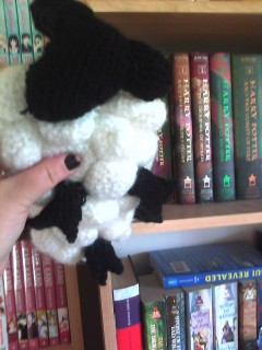 Crocheted dreamsheep being held up in Azz's black-nail-polished hand.