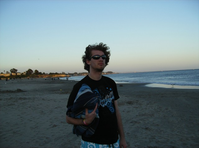 JD on the beach with the ocean behind him at sunset. Full length, profile. He is wearing sandals, long tropical-flowered blue and white swimming shorts, a dark t-shirt, and sunglasses, carrying a towel. His curly hair is shaggier than usual and its natural dark blond; he has a week's worth of beard stubble.