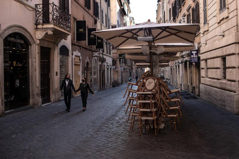 Пара прогуливается по пустынной улице в Риме во вторник.
