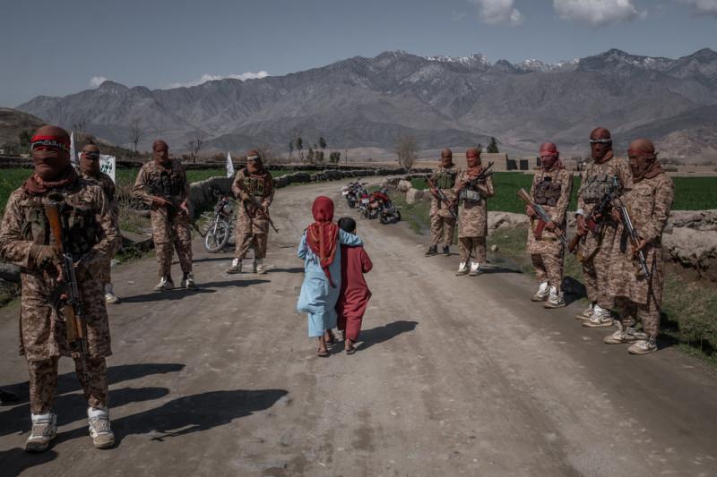 Два мальчика проходят мимо членов Красного отряда талибов, элитных сил, в районе Алингар в марте. Джим Хейлбрук для Нью-Йорк Таймс