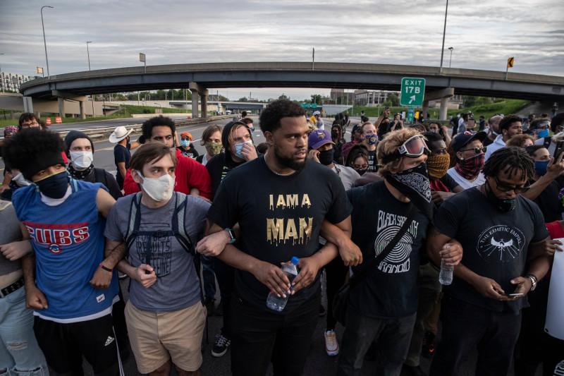Демонстранты маршируют по шоссе I-35 в Миннеаполисе в воскресенье