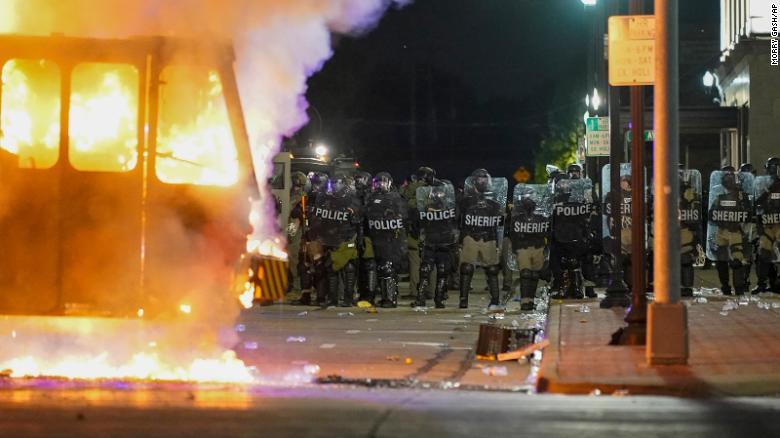 Полиция стоит возле горящего мусоровоза во время протестов в понедельник в Кеноша