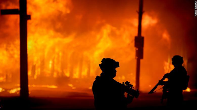 Полиция стоит возле здания, которое загорелось во время протестов в понедельник в Кеноша