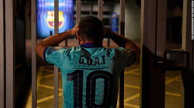 Один фанат «Барселоны» с надписью «Greatest Of All Time» на футболке выглядит удрученным за пределами Камп Ноу.