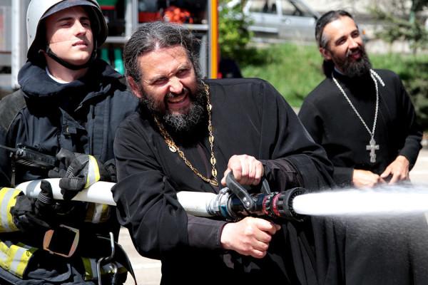 Священнослужители и сотрудник МЧС во время учений по ликвидации пожаров. Фото Алексей Павлишак ТАСС