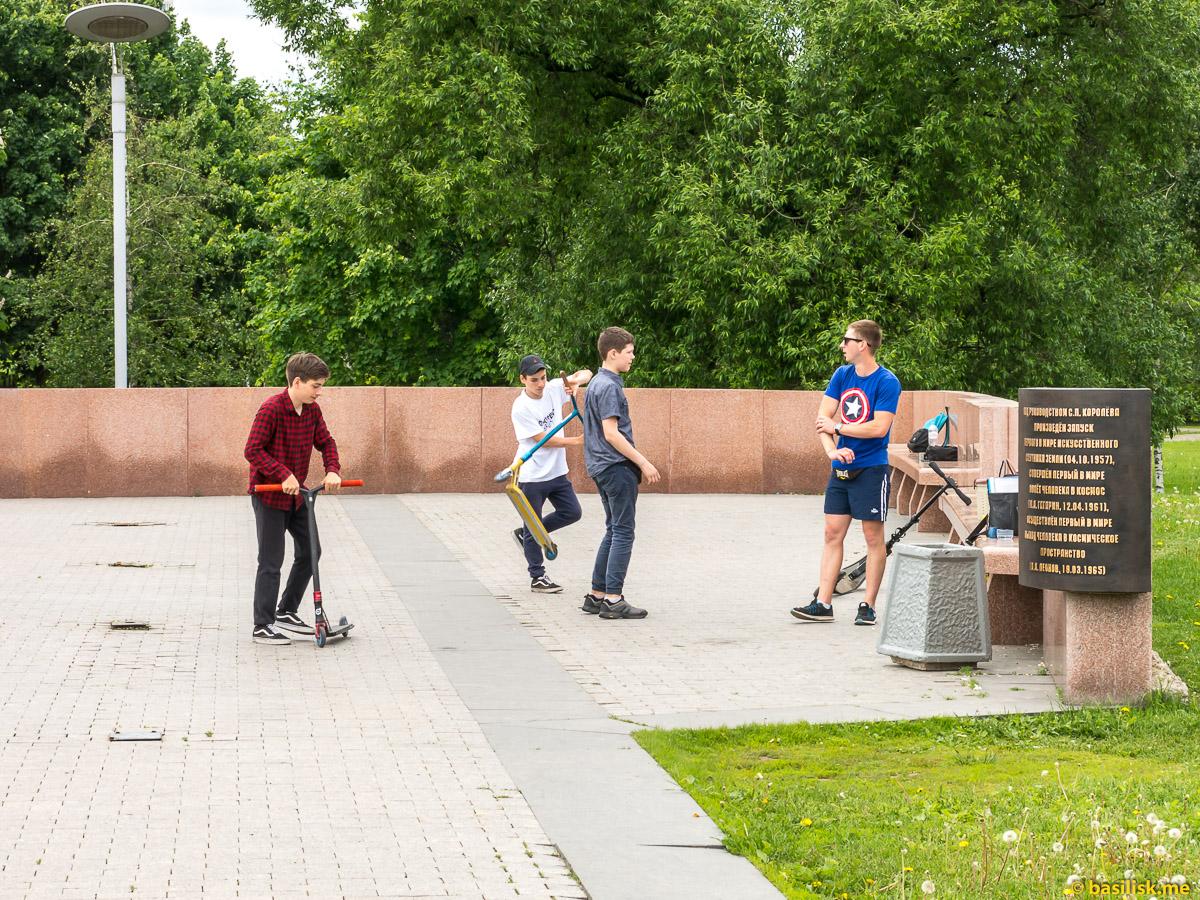 Мальчишки катаются на самокатах. Парк и аллея Космонавтов. Монумент Покорителям космоса. Москва. Май 2018