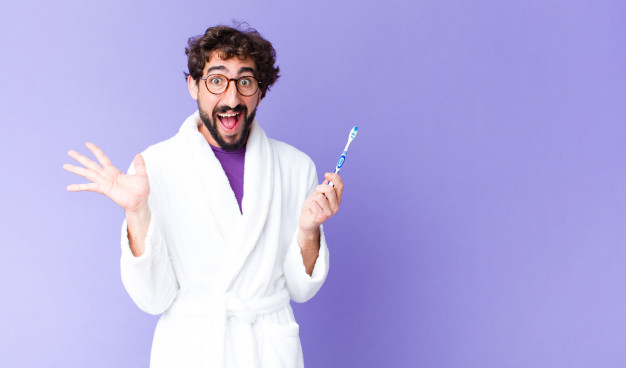 young-crazy-bearded-man-wearing-bathrobe-and-a-teeth-brush_1194-107977